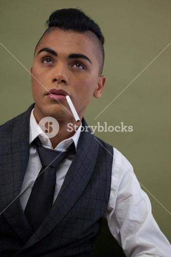Transgender with cigarette in mouth looking away