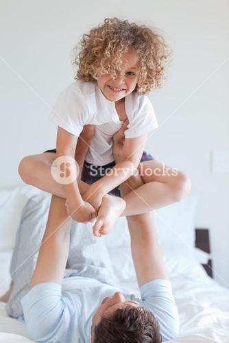 Father lifting child on bed