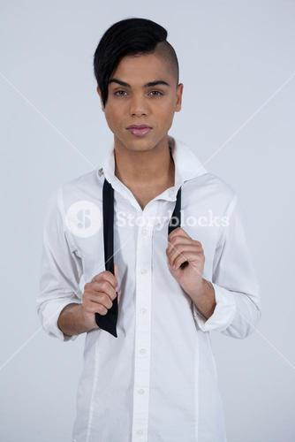Portrait of confident transgender female holding tie