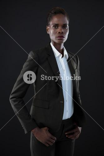 Androgynous man in suit posing against grey background
