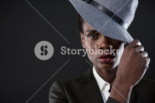 Androgynous man with hand on hat against grey background