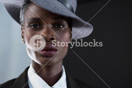 Androgynous man in hat against grey background