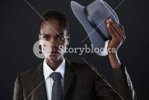 Androgynous man holding a hat against grey background