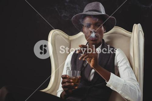 Androgynous man smoking cigar while while sitting on a chair