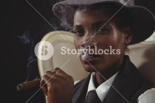 Androgynous man smoking cigar while sitting on a chair