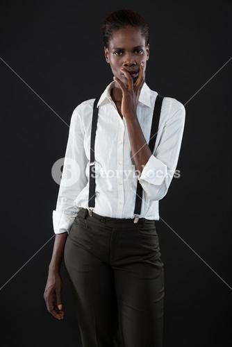 Androgynous man standing with hands on his face