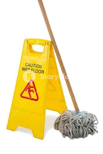 Close up of wet floor sigh board with mop