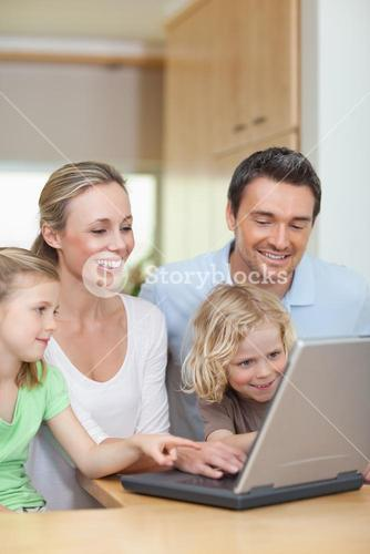 Family using laptop in the kitchen