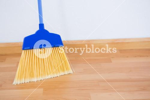 Close up of broom on hardwood floor