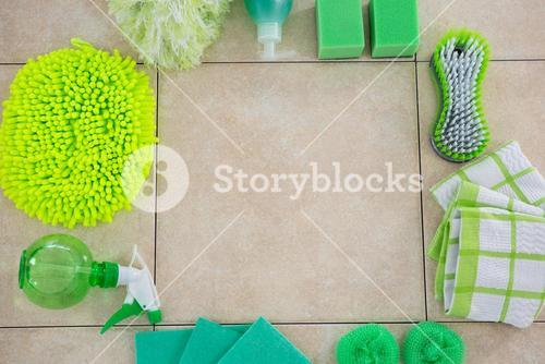 Overhead view of green cleaning products arranged floor