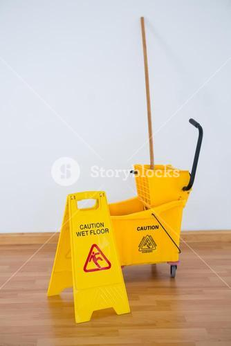 Sigh boad with mop bucket against wall