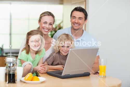 Smiling family using the internet in the kitchen