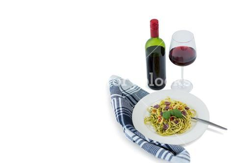Pasta served in plate by wineglass