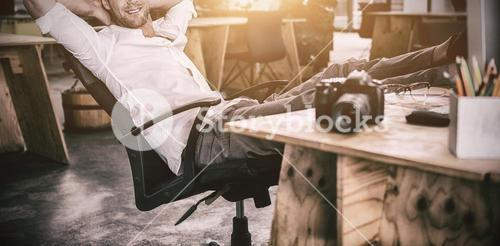 Smiling businessman relaxing on the chair