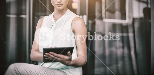 Businesswoman using digital tablet while sitting on chair