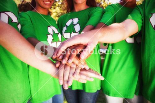Midsection of volunteers stacking hands