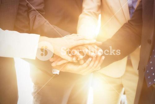 Midsection of business people stacking hands