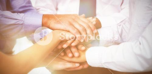 Close-up of coworkers stacking hands