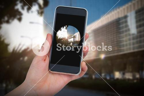 Composite image of hand holding mobile phone against white background
