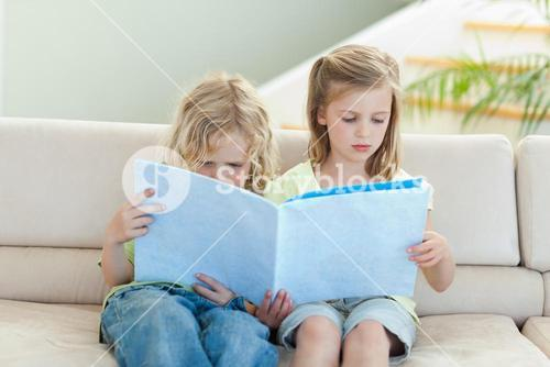Siblings reading magazine on the sofa