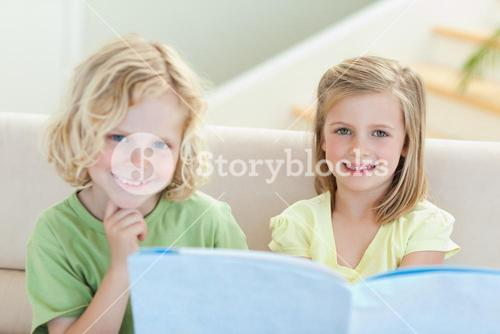 Siblings on the couch reading magazine
