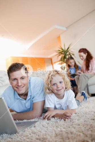 Father and son using internet on the floor