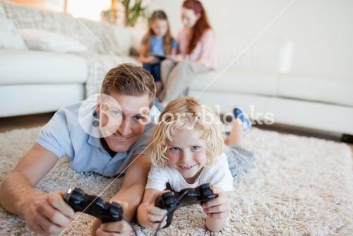 Father and son in the living room playing video games