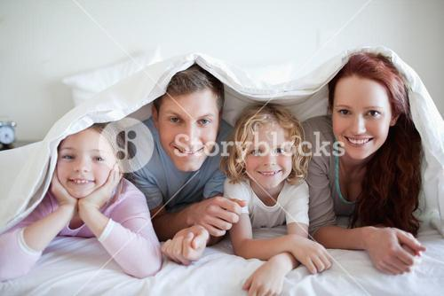 Happy family under bed cover