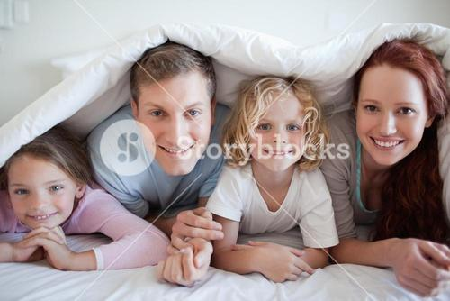 Smiling family under bed cover