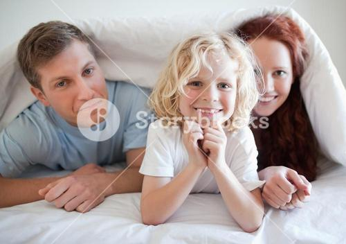 Boy with his parents under bed cover