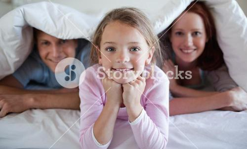 Girl under bed cover with parents
