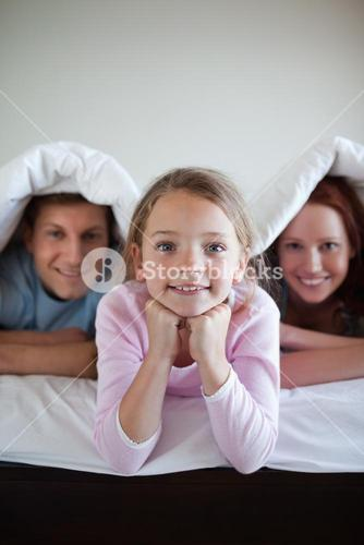 Smiling girl under bed cover with her parents