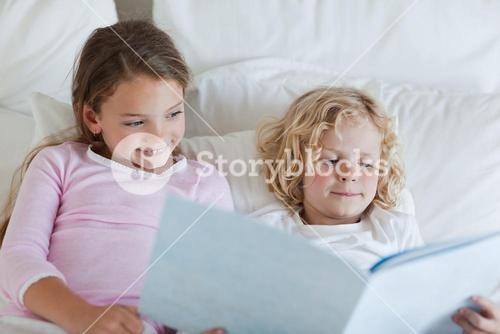Brother and sister reading bed time story
