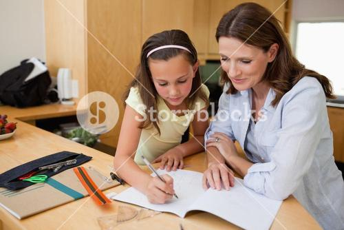 Girl doing homework with her mother