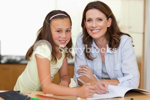 Woman helping her daughter with homework