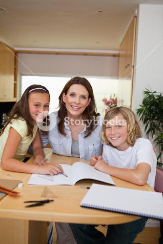 Siblings getting help with homework from mother