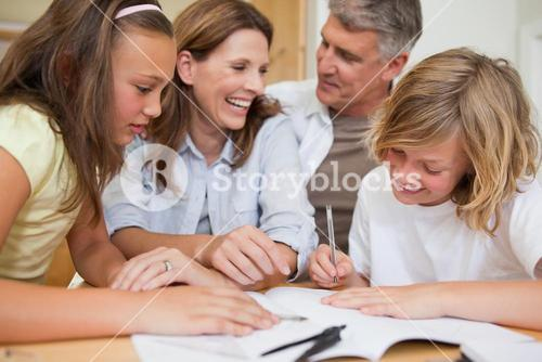 Siblings getting help with homework from parents