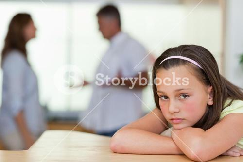 Sad girl with fighting parents behind her