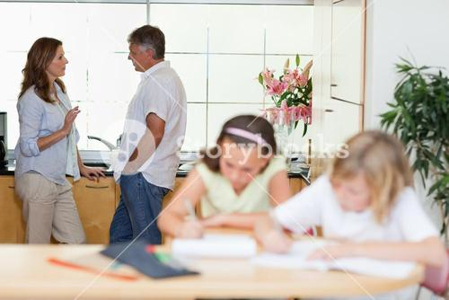 Parents talking with children doing homework in front of them