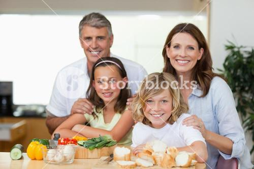 Smiling family making sandwiches