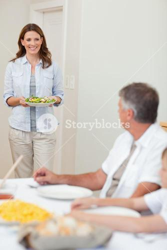 Mother bringing salad to the dinner table