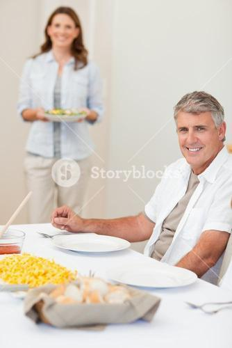 Man waiting for his wife to bring salad to the table