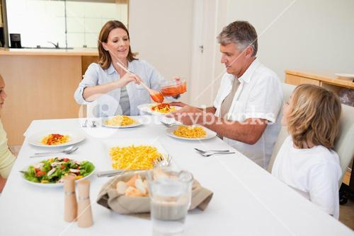 Woman serving dinner to family