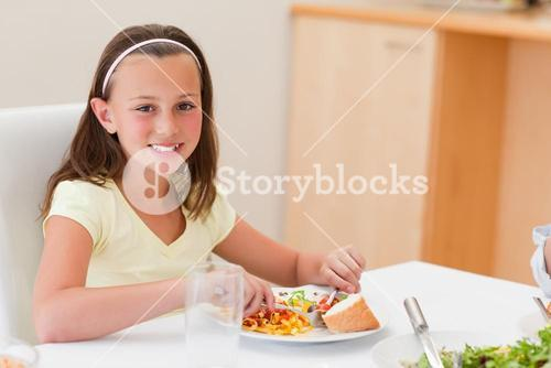 Smiling girl having dinner at dinner table