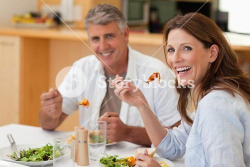 Laughing couple eating dinner