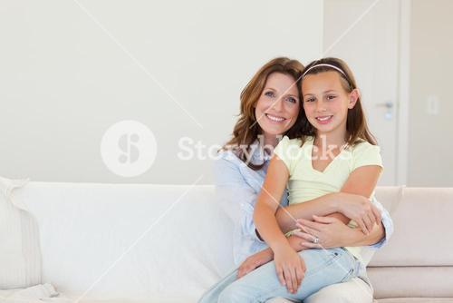 Smiling mother and daughter embracing