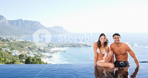 Couple sitting on pool edge with landscape in the background