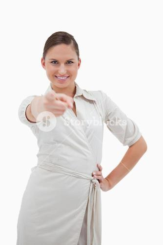 Portrait of a smiling businesswoman pointing at the viewer