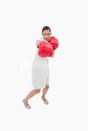 Portrait of a businesswoman punching someone
