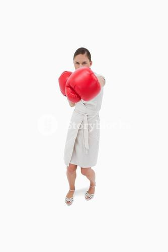 Portrait of a serious businesswoman punching someone